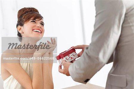 Man giving smiling girlfriend present