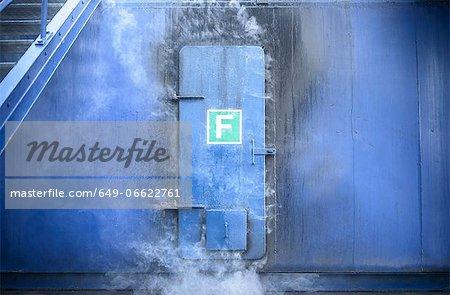 Smoke pouring from behind steel door