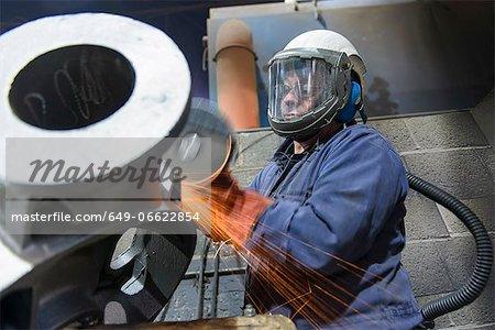 Worker grinding casing in metal foundry