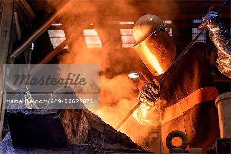 Worker stirring molten metal in foundry