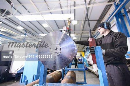Worker using crane in steel factory