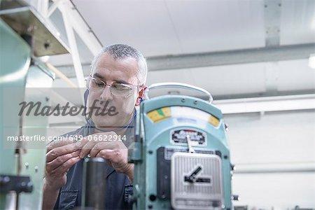 Worker polishing steel parts in factory