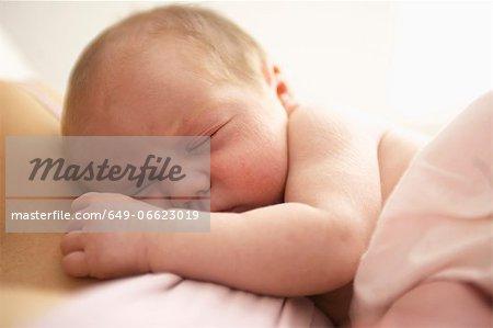 Baby girl sleeping on her mother