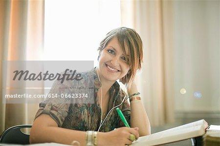 Woman in earphones studying at desk