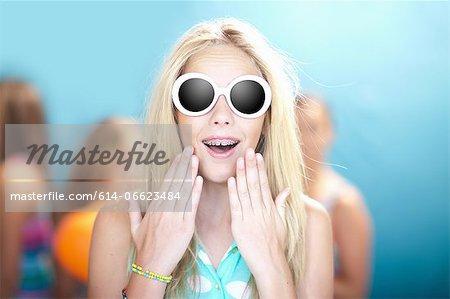 Teenage girl in sunglasses gasping