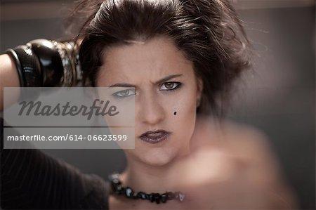 Teenage girl in dark makeup pointing