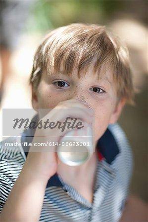 Boy drinking soda outdoors