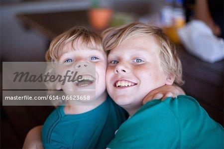 Smiling boys hugging in living room