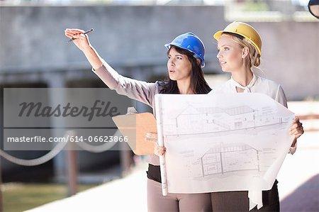 Businesswomen reading blueprints