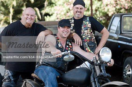 Men smiling around motorcycle