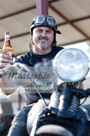 Man drinking beer on motorcycle