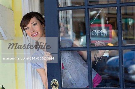Woman hanging open sign in door