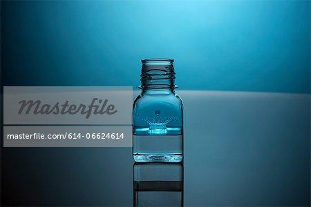 Drop splashing in glass bottle