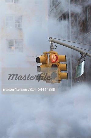Traffic light on steamy city street