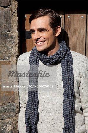 Smiling man wearing scarf outdoors