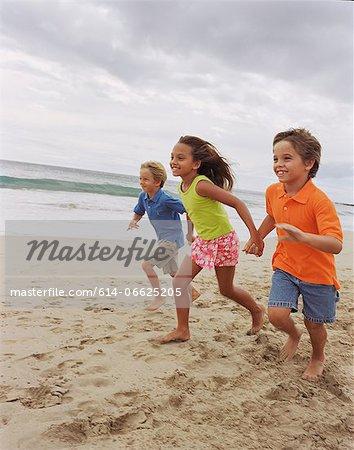 Children running together on beach