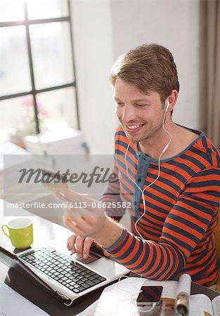 Man in headphones shopping on laptop