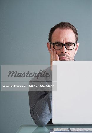 Businessman Using Computer in Studio