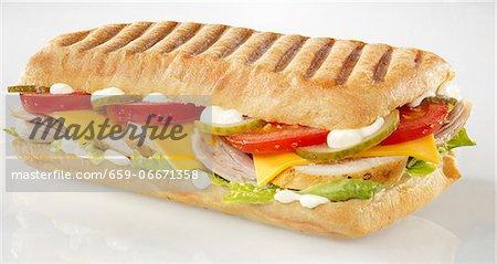 Chicken, tomato, gherkin, cheese slice and lettuce panini