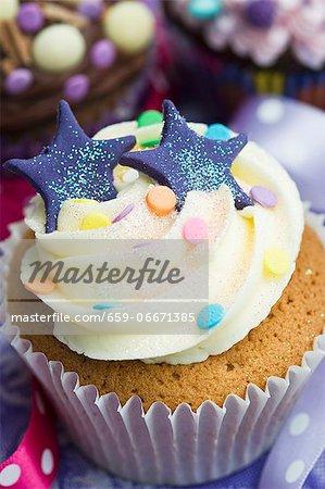 A vanilla cupcake with blue stars, glitter and sugar confetti