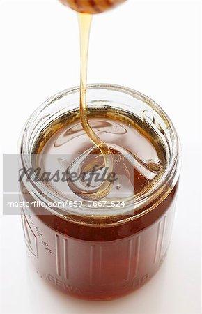 Honey trickling from a honey dipper into a jar