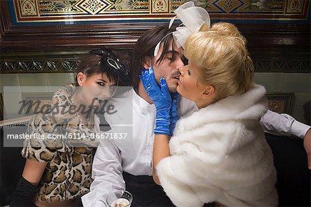 Two lavishly dressed women flirting with a man