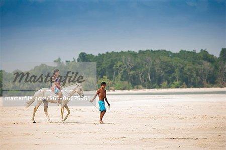 South America, Brazil, Para, Amazon, Marajo island, local man leads a girl on horseback across a beach near Soure