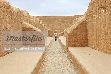 South America, Peru, La Libertad, Trujillo, a tourist walks along a corridor in the UNESCO World Heritage listed Chan Chan archaeological sit