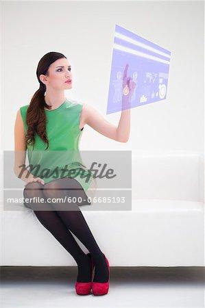 Young Businesswoman Sitting on Sofa using Digital Display, Studio Shot on White Background