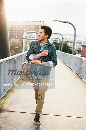 Smiling young man walking on foot bridge.