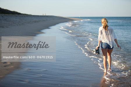 Young Woman Carrying Camera while Walking along Beach, Palm Beach Gardens, Palm Beach, Florida, USA