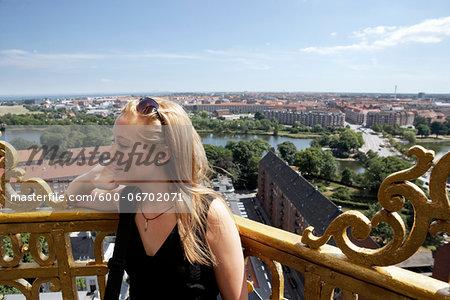 Young woman enjoing the view from Vor frelsers kirke tower at Christianshavn, Copenhagen, Denmark.