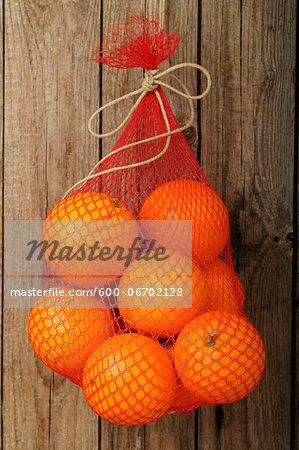 Bag of Oranges Hanging on Wall, Studio Shot