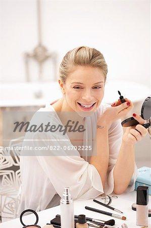 Woman at Dressing Table Applying Mascara