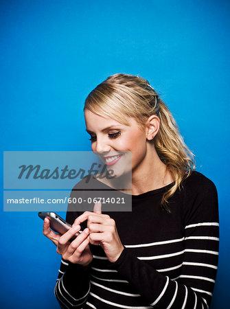Young Woman using Smart Phone, Studio Shot