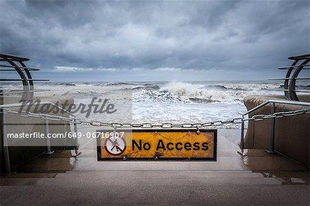 """No access"" sign at stormy beach"