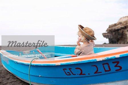 Toddler girl sitting in boat on beach