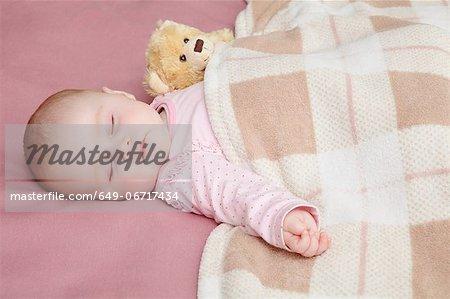 Baby girl sleeping in bed