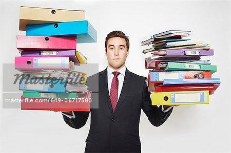 Businessman balancing stacks of folders