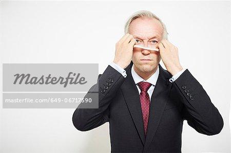 Businessman pulling on mask