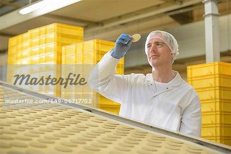 Worker examining biscuit in factory