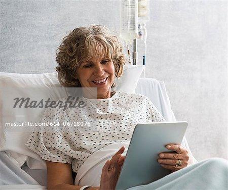 Female hospital patient using digital tablet