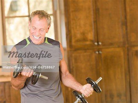 Older man lifting weights at home
