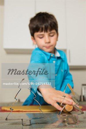 Boy using cookie cutters in kitchen