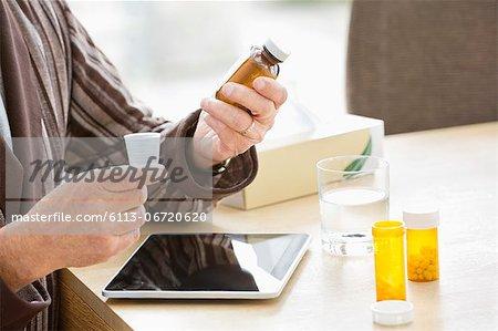 Older man taking medications at table
