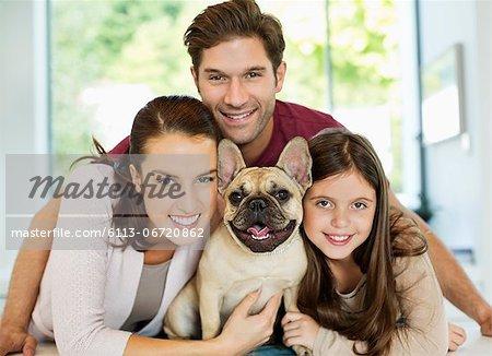 Smiling family hugging dog