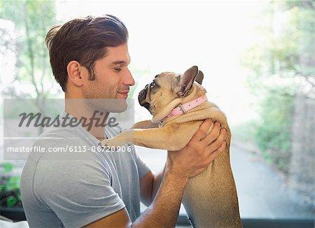 Smiling man holding dog indoors