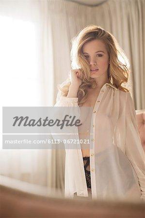 Woman wearing sheer top in bedroom