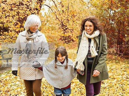 Three generations of women walking in park