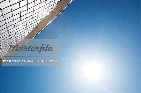 Sun by modern building in blue sky